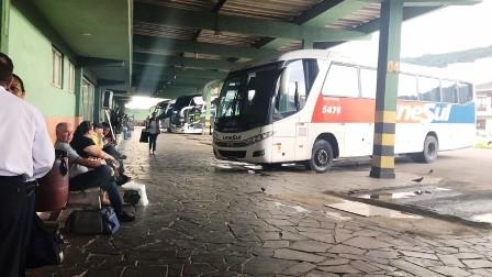 Rodoviária de Osório com ônibus e passageiros em bancos à espera